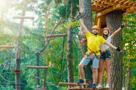 Young woman and man in protective gear are standing on wooden board on high tree, posing and smiling. Rope adventure park with obstacles and ziplines. Extreme rest and summer activities concept.