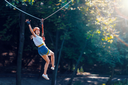 Happy women girl female gliding climbing in extreme road trolley zipline in forest on carabiner safety link on tree to tree top rope adventure park. Family weekend children kids activities concept Foto de archivo
