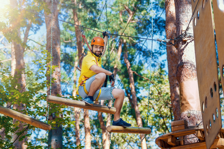 Young smiling man, in protective gear, is sitting on rope trail, bridge on high trees in forest. Rope adventure park with difficult obstacles and ziplines. Extreme rest and summer activities concept. Stock Photo