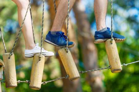 Closeup of female and male legs in sneakers keep balance on wooden stumps hanging on ropes on high trees in park. Rope park with obstacles and ziplines. Extreme rest and summer activities concept.