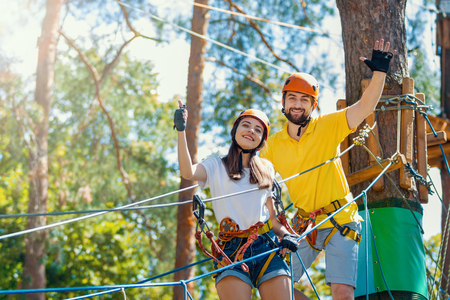 Young woman and man in protective gear are standing on rope bridge hanging on high trees, posing and smiling. Rope park with obstacles and ziplines. Extreme rest and summer activities concept. Stock Photo