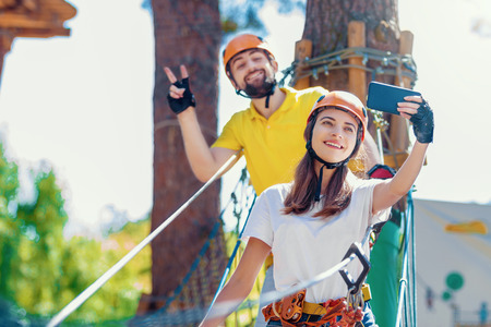 Young woman and man in protective gear are standing on rope bridge hanging on high trees, making selfie and smiling. Rope park with obstacles and ziplines. Extreme rest and summer activities concept.