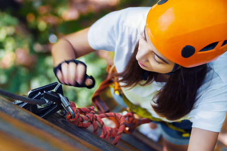 Young adult female woman climber with protective sport equipment and helmets climbs and enjoys active leisure in extreme rope park at green forest in summer. Active and healthy lifestyle concept