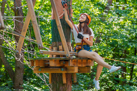 Young beauty female woman adult wears protective helmet having fun in extreme rope park, amusement park. Sitting in rope bridge at green nature forest. Active healthy lifestyle in spring or summer. Stock Photo