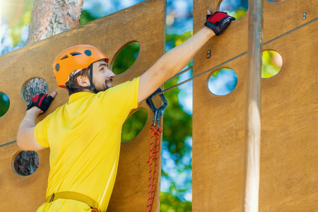 Young male man adult wears protective helmet with action camera having fun in extreme rope park, amusement park. Climbing in wooden wall at green forest. Active healthy lifestyle in spring or summer. Stock Photo