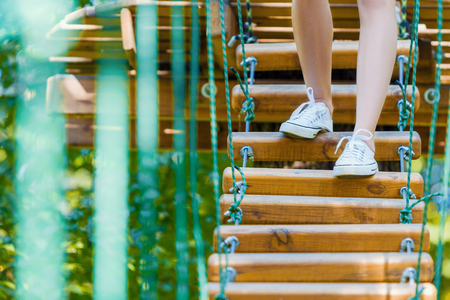 Slender female legs in white sneakers walking and keep balance on rope bridge on high trees in park. Rope park with difficult obstacles and ziplines. Extreme rest and summer activities concept.