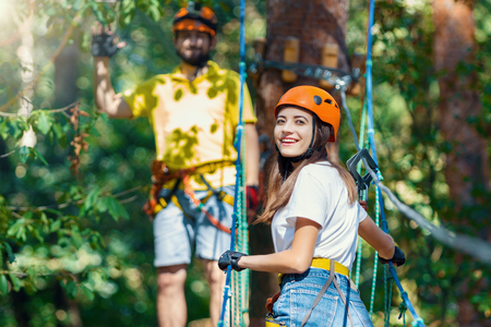 Woman, in protective gear and helmet, climb rope bridge on high trees, her friend instructor on background. Rope adventure park with obstacles and ziplines. Extreme rest and summer activities concept