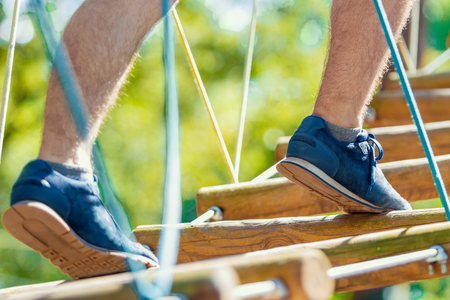 Closeup male legs in blue sneakers walking and keep balance on rope bridge on high trees in park. Rope park with different obstacles and ziplines. Extreme rest and summer activities concept. Stock Photo