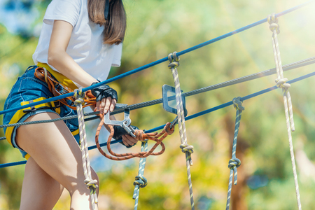 Young beauty female woman adult wears protective helmet having fun in extreme rope park, amusement park. Climbing in rope bridge at green nature forest. Active healthy lifestyle in spring or summer.