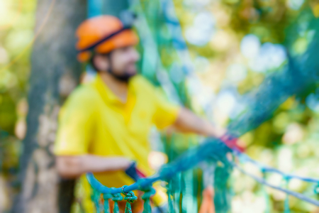 Young male man adult wears protective helmet with action camera having fun in extreme rope park, amusement park. Climbing in rope bridge at green forest. Active healthy lifestyle in summer. Bokeh Stock Photo