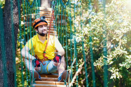 Young adult male man climber with protective sport equipment and helmets climbs and enjoys active leisure in extreme rope park at green forest in summer. Active and healthy lifestyle concept