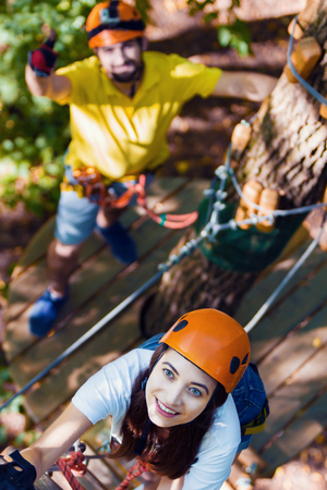 Young adult couple in love, climbers with protective sport equipment and helmets climb and enjoy active leisure in extreme rope park at green forest in summer. Active and healthy lifestyle concept