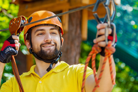 Portrait men boy male climbing in extreme road trolley zipline in forest. Gliding carabiner safety link on tree to tree top rope adventure park. Family weekend vacation children activities concept