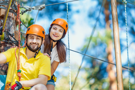 Young woman and man in protective gear are sitting on rope bridge hanging on high trees, posing and smiling. Rope adventure park with obstacles and ziplines. Extreme rest and summer activities concept Stock Photo
