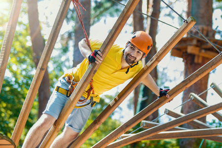 Young male man adult wears protective helmet with action camera having fun in extreme rope park, amusement park. Climbing in rope bridge at green forest. Active healthy lifestyle in spring or summer.
