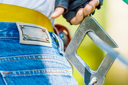Close-up of metal protective fastening for extreme climbing worn by young female woman adult in blue jeans shorts in extreme rope park at green forest. Active safe extreme lifestyle in summer, spring
