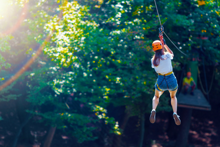 Happy women girl female gliding climbing in extreme road trolley zipline in forest on carabiner safety link on tree to tree top rope adventure park. Family weekend children kids activities concept Stock Photo