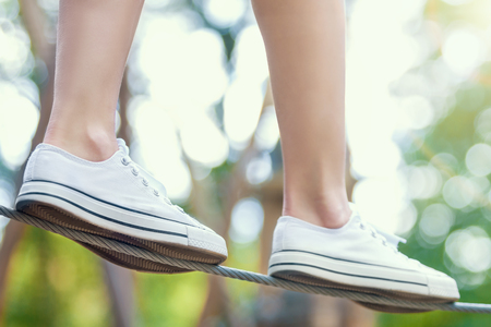 Closeup female slender legs in white sneakers walking and keep balance on thin ropes on high trees in park. Rope park with different obstacles and ziplines. Extreme rest and summer activities concept.