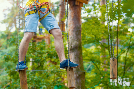 Male legs in blue sneakers keep balance on wooden stumps hanging on ropes on high trees in park. Rope park with different obstacles and ziplines. Extreme rest and summer activities concept.