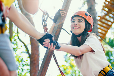 Couple in love man male and woman female adults wear protective helmets and having a date in extreme rope park at green forest. Climbing in rope bridge. Active healthy extreme lifestyle leisure.