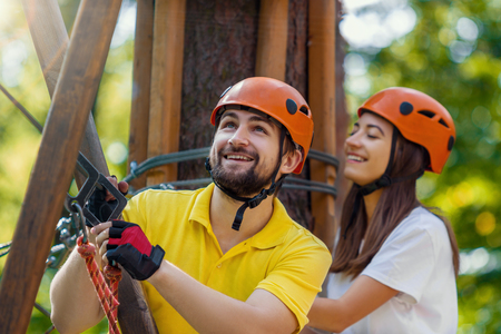 Young woman and man, in protective gear and helmets, climb rope trail and smile on high trees on forest. Rope adventure park with obstacles and ziplines. Extreme rest and summer activities concept. Stock Photo