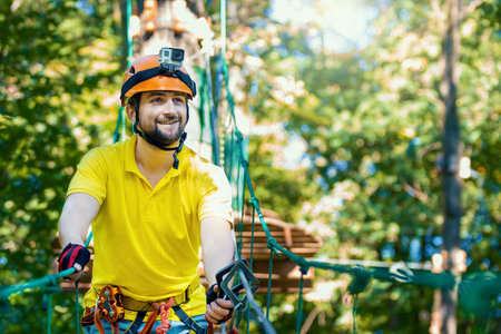 Young smiling man with action camera, in protective gear, climb rope trail, bridge on high trees. Rope adventure park with obstacles and ziplines. Extreme rest and summer activities concept. Stock Photo
