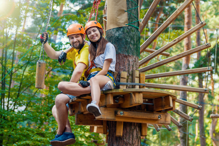 Young woman and man in protective gear are sitting on wooden board on high tree, posing and smiling. Rope adventure park with obstacles and ziplines. Extreme rest and summer activities concept.