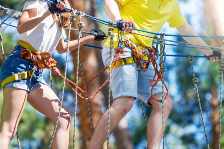 Young woman and man, in protective gear, climb rope trail, bridge on high trees on forest. Rope adventure park with different obstacles and ziplines. Extreme rest and summer activities concept. Stock Photo