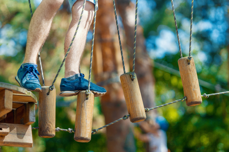 Closeup of male legs in blue sneakers keep balance on wooden stumps hanging on ropes on high trees in park. Rope park with obstacles and ziplines. Extreme rest and summer activities concept. Stock Photo
