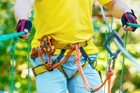 Close up of gliding carabiner safety link on tree to tree top rope adventure park. Men boy male climbing in extreme road trolley zipline in forest. Family weekend vacation children activities concept