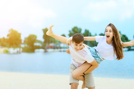 Young couple in love female girl and male man teenagers adults having fun and enjoying weekends near water, river, lake at hot sunny summer day at sand beach. Summer hobbies leisure activities concept 写真素材