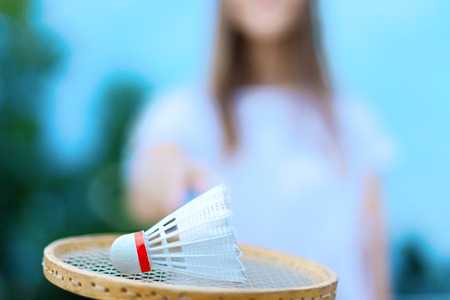 Closeup of white shuttlecock lying on wooden badminton racket. In defocus silhouette of young woman female in light clothes is holding racket on her outstretched hand. Summer activities concept. Stock Photo