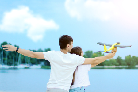 Young couple in love female girl and male man teenagers adults having fun with launching polyfoam airplane toy and enjoying weekends near water, river, lake at hot sunny summer day at sand beach.