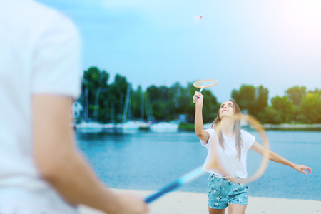 Young couple in love female girl and man male teenagers adults playing in badminton with rackets and shuttlecock near water, river, lake at hot summer day at beach. Summer activities, leisure concept.