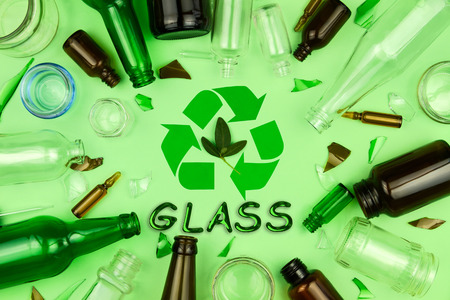 Glass garbage on background. Recycling reuse symbol sign with inscription and leaves in center, surrounded with green,brown, transparent bottles and jars. Trash sorting at home. Save planet concept. Reklamní fotografie