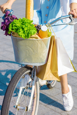 Closeup of basket of groceries with baguette, basil leaves, lettuce, bottle of juice, attached to handlebars. Woman is going to grocery store on vintage retro white female bicycle. Cycling in city.