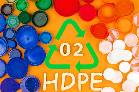 Plastic colorful reusable hdpe bottle caps around recycling sign with code 02. Nature pollution contamination, ecology environmental problem damage concept. Orange background. Secondary raw materials
