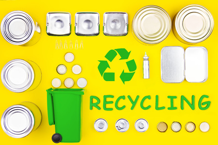 Aluminum metal reusable tin cans bottle caps recycling sign symbol Nature pollution contamination ecology environmental problem damage concept Secondary raw materials yellow background perfectionism