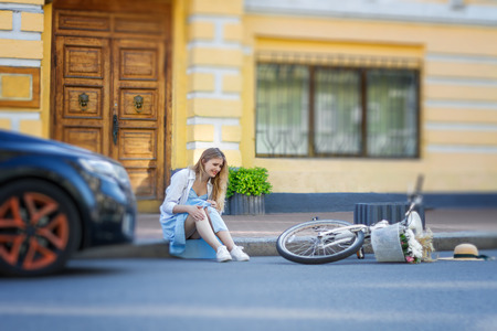 Young woman had accident while rolling on female bicycle. Beautiful girl sitting and crying on roadside. Broken bike lying on road in front of car. Ecological transport in city. Urban traffic concept. 写真素材