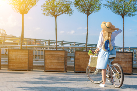 Happy smiling woman girl dressed stylish retro pin up cloth dress riding white bicycle with basket of fruits and color bags on handlebars. Warm summer spring autumn day. Green shopping trip concept.