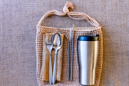 Bag with picnic set on background of burlap. Alternative to disposable tableware. Thermo cup, metal straw with brush, spoon, fork and reusable napkin. Zero waste and plastic free concept.