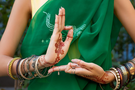 Beautiful woman in traditional Muslim Indian wedding green sari dress costume with henna tattoo jewelry and bracelets do hands nritta odissi Samyuta hastas dance Movement araala Concept background Stock Photo