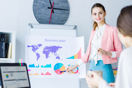 Beautiful smiling professional woman in colorful strict cloth share presentation, business plan, idea in modern office meeting room with colleagues Big boss, team worker, clerk, employee, sync concept