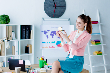 Young lazy business woman in pink blazer is idling at workplace. Beautiful girl employee is smiling and doing makeup sitting on desk in modern office. Relax time at job. Bad worker concept.