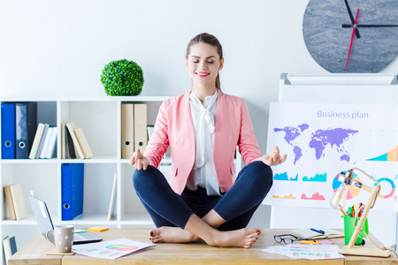 Young beautiful business woman boss in pink blazer is sitting in lotus position on desk, workplace. Girl employee is meditating and having moment of relaxation at modern office. Stress job concept.