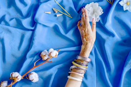 Slender female hand painted with Indian oriental mehndi ornaments by henna. Hand dressed in bracelets and rings hold white flower. Blue fabric with folds and cotton branches on background.