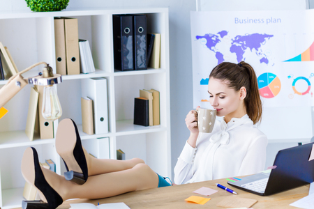 Happy positive employee boss worker, clerk relaxing has break lunch coffee time at work. Beautiful woman sitting at office workplace hold cup of tea and smell sniff tasty drink Meditation culm concept