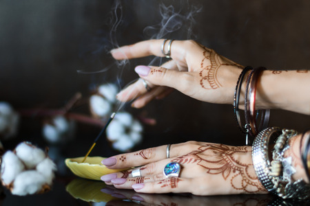 Closeup of female wrists painted with henna traditional Indian oriental mehndi ornaments. Hands dressed in bracelets and rings put aromatic stick in stand.  Branch with cotton flowers on background. Stok Fotoğraf