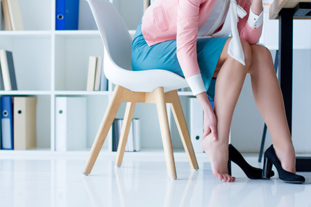 Business woman in strict colorful clothes sitting in chair, hold legs has pain varicose veins symptom, arthritis, arthrosis, joint disease from black high heels. Office worker health problem concept. Stock Photo
