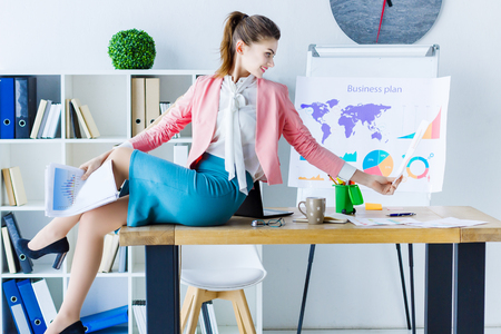Beautiful professional business woman in glasses and colorful cloth sitting on table in modern office browse documents, materials preparing presentation. Big boss, team worker, clerk, employee concept